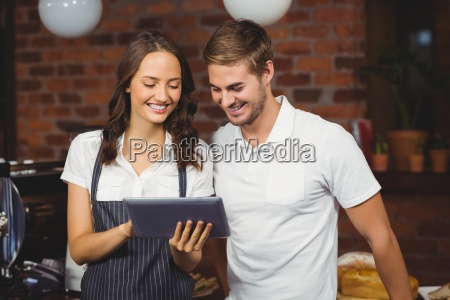 smiling co workers using a tablet