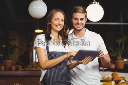 smiling co workers holding a tablet