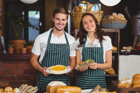 smiling co workers showing sandwich and