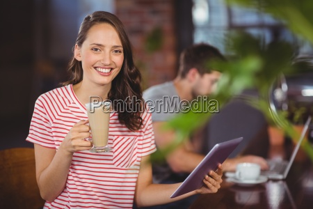 smiling young woman enjoying latte and