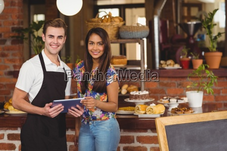smiling waiter and pretty customer looking