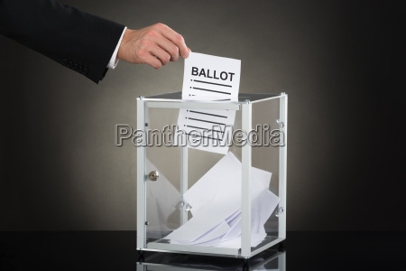 wirtschaftler hand putting ballot in glass