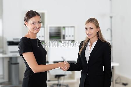business women shaking hands making a
