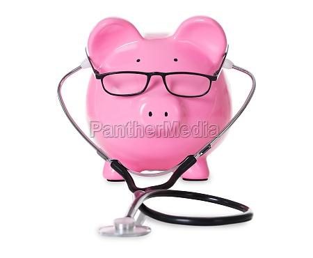 piggybank with stethoscope and eyeglasses