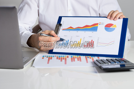 businessman showing financial charts at desk