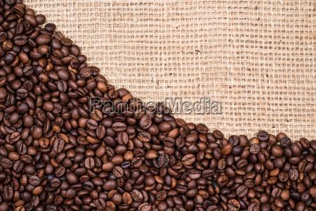 kaffeebohnehintergrund mit juteleinwandgewebe