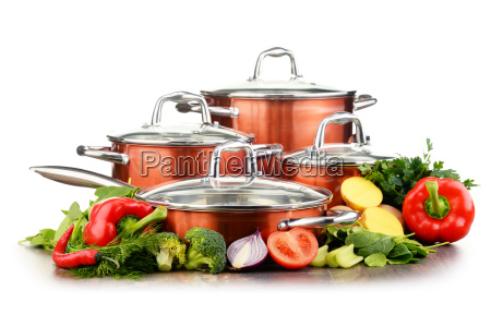 set of pots and raw vegetables
