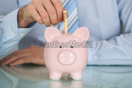 businessman inserting note in piggy bank