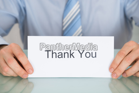 businessman holding card with thank you