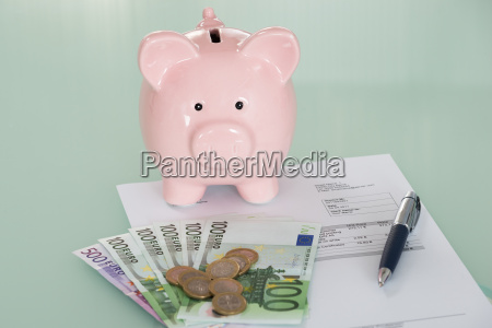 piggybank and currency on desk