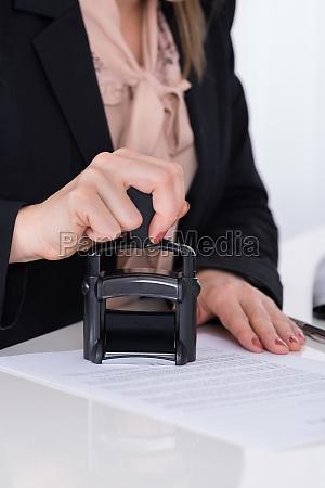 wirtschaftler mit stamper auf dem dokument