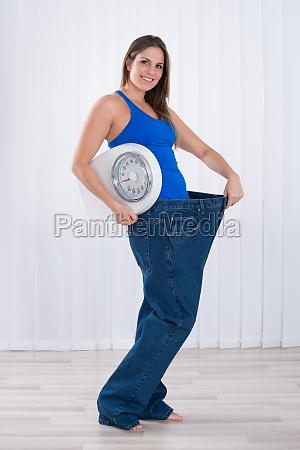woman with weighing machine wearing big