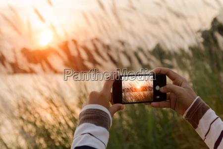 nahaufnahme hand mit telefon aufnahme landschaftsfoto