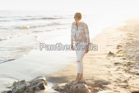 woman walking along a sandy beach