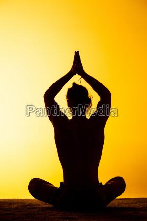 der mann der yoga im sonnenuntergangslicht