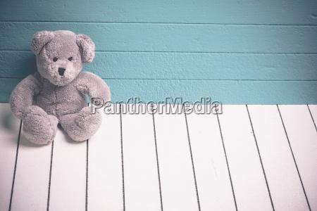 teddybaer sitzt auf weissen holzboden mit