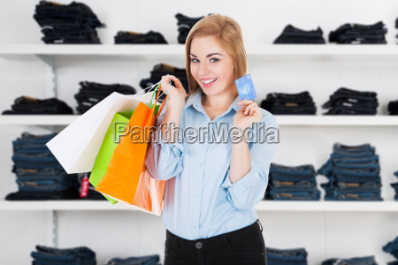 happy woman holding credit card in