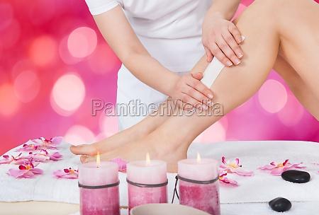 beautician waxing womans leg in beauty