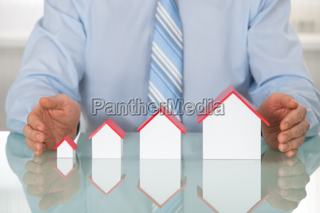 businessman protecting house models