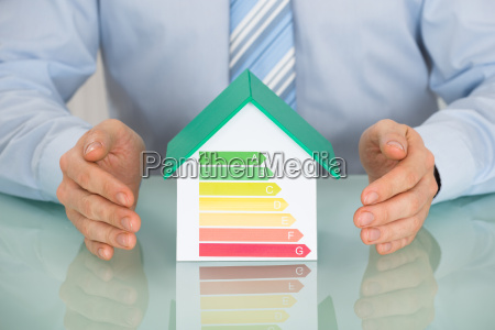 businessperson protecting house model