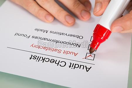 person filling audit checklist form