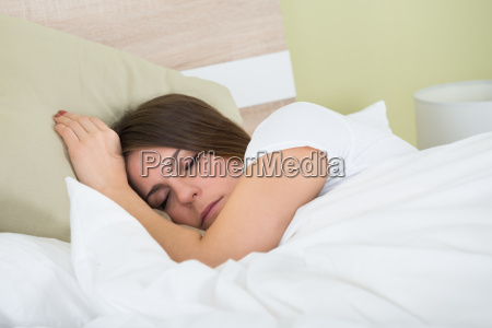 frau schlafend auf bett mit einer