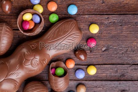 schokoladen ostereier und suessigkeiten auf holzuntergrund