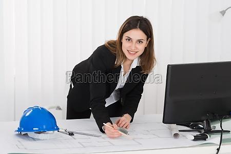 female architect working on blueprint