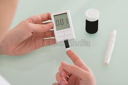 patient hand checking blood sugar level