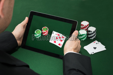 poker hand with digital tablet showing