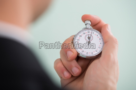 person hand holding stopwatch