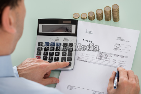 businessperson calculating invoice with coins at