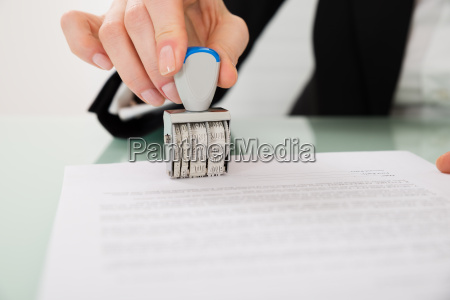 businesswoman hand stamping paper with date