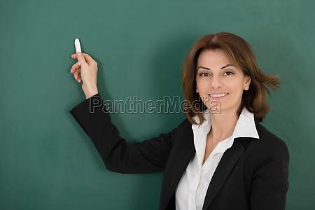 happy female teacher holding chalk
