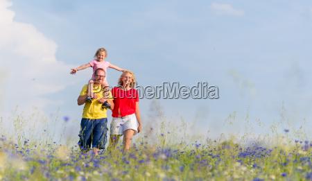familie macht spaziergang auf wiese mit