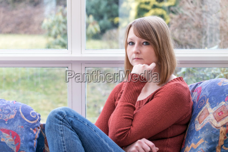 young woman is pensively looking at