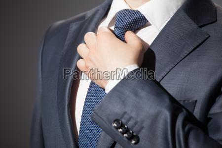 geschaeftsmann passt seine krawatte an