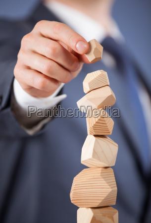 unerkennbarer geschaeftsmann der eine hoelzerne pyramide