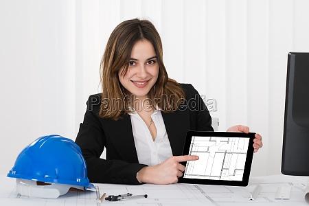 female architect pointing at blueprint on