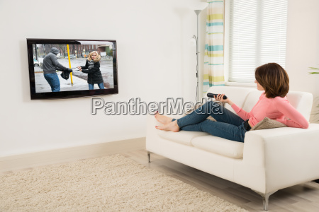 woman holding remote while watching television
