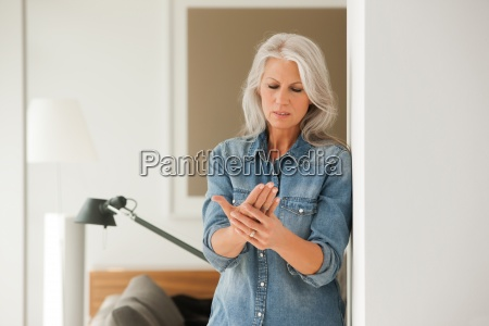senior woman with hand pain standing