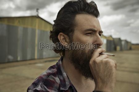 man with full beard smoking cigarette
