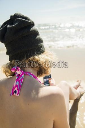 teenage girl sitting at waterside of