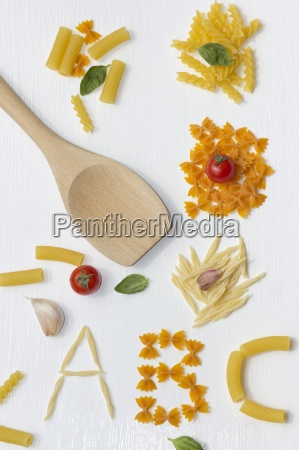 different noodles and wooden spoon on