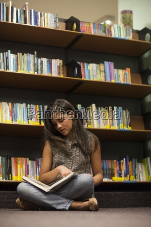teenage girl in a library reading