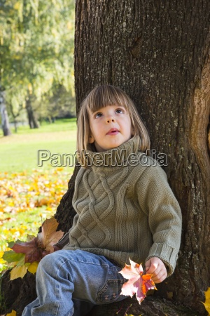 little girl leaning at tree trunk