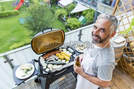 lächelnd, mant, grillen, auf, seinem, balkon - 16349505