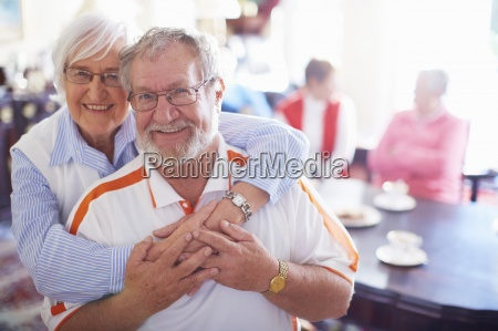 happy senior couple with friends in