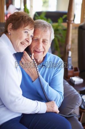 glueckliche aeltere paare sharing telefonhoerer zu
