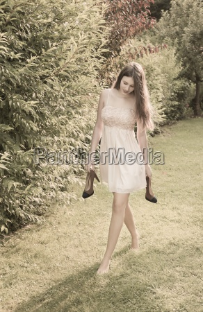 young woman walking barefoot on meadow
